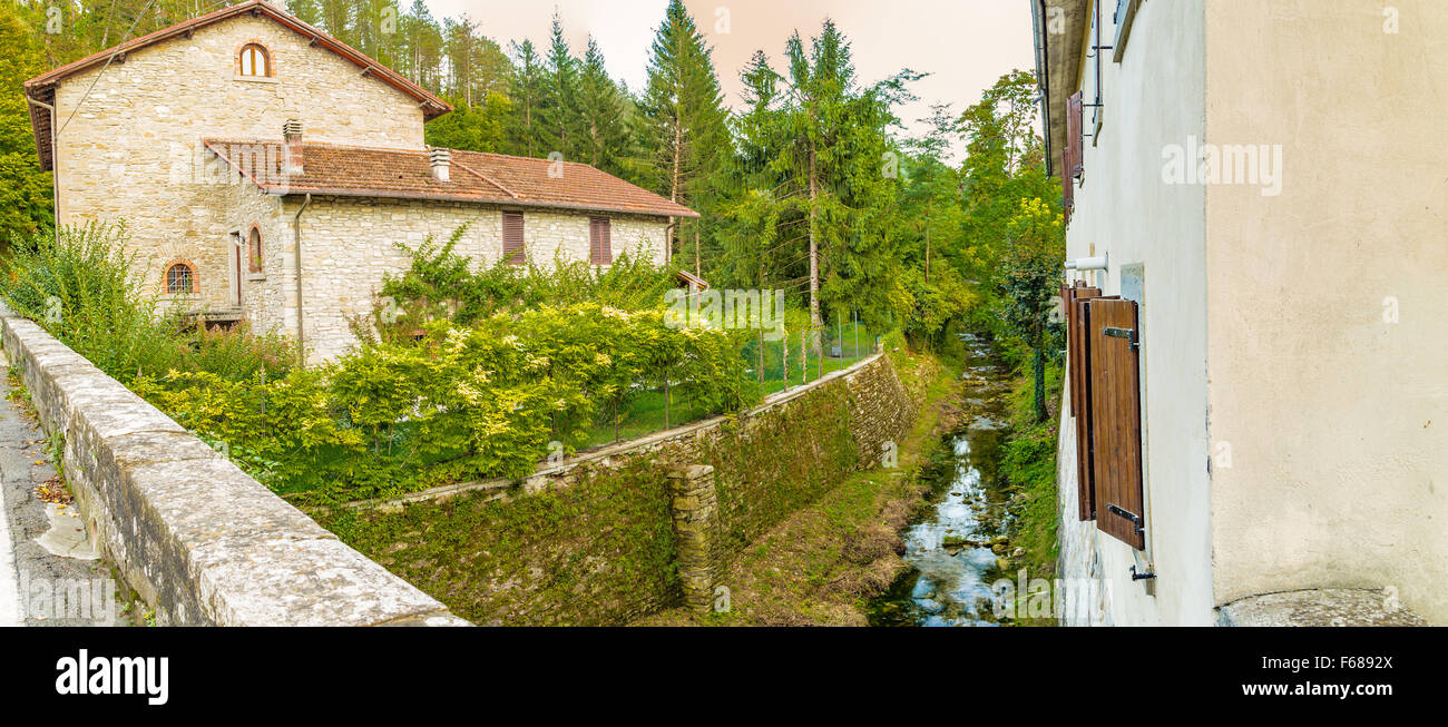 Small stream runs trhough medieval mountain village in Tuscany characterized by houses with walls of stones derived Stock Photo