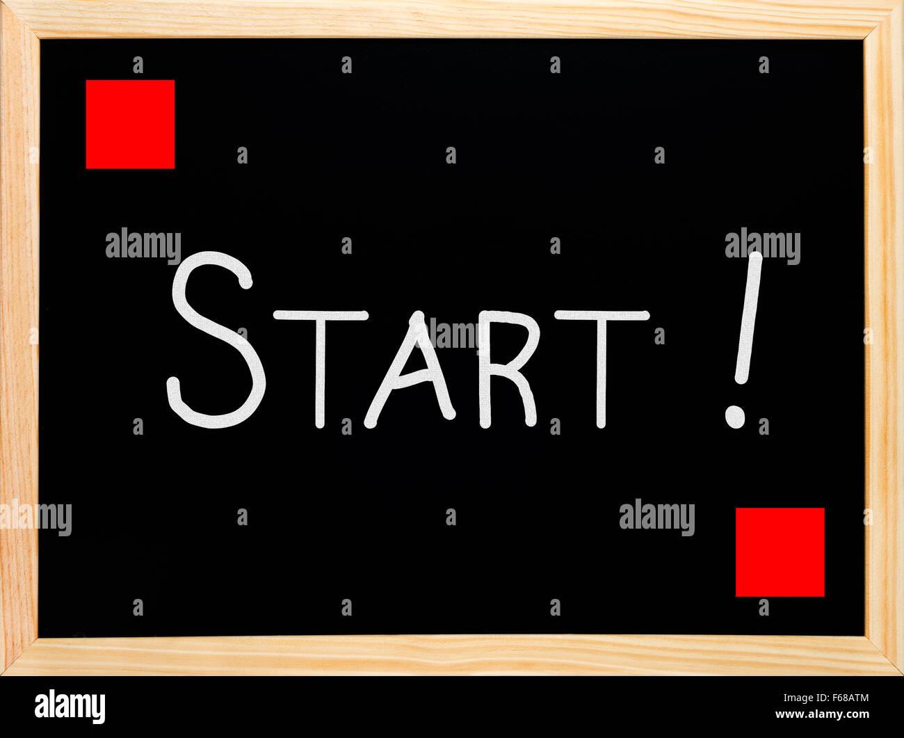 Start and red flag written on blackboard or chalkboard - Stock Image