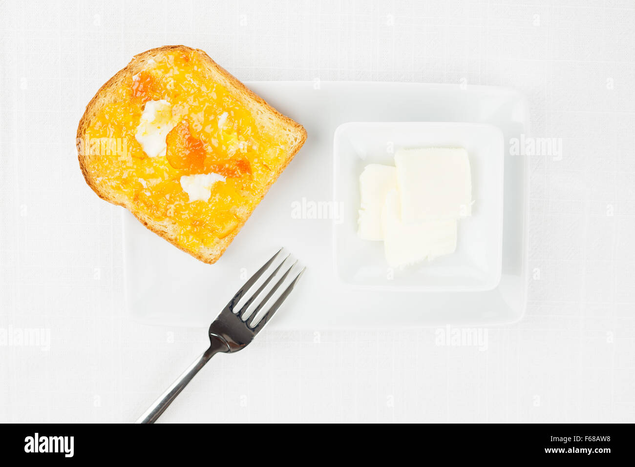 French toast with spread bitter orange marmalade or jam with candied peel, butter curls, fork and dishware on white - Stock Image