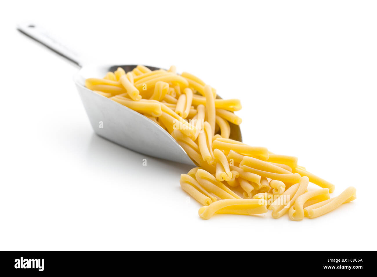 uncooked pasta caserecce in metal scoop on white background - Stock Image
