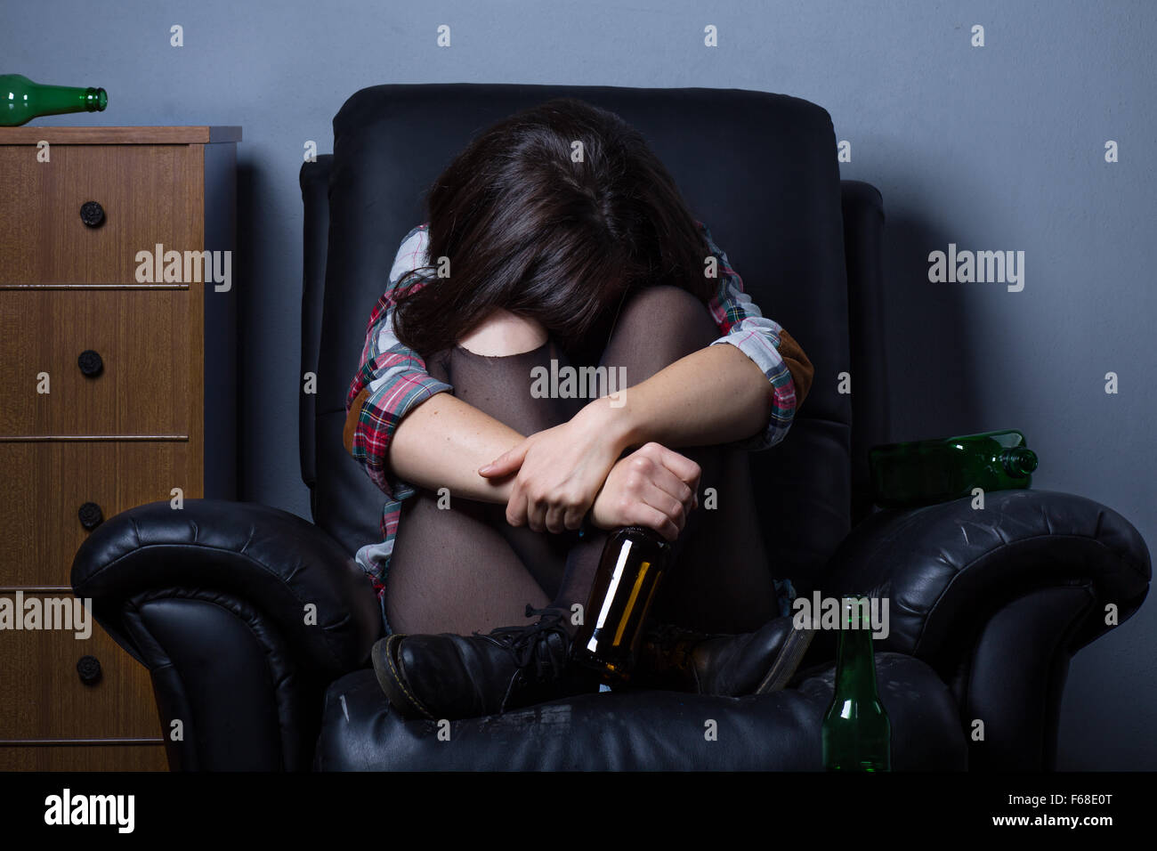 Sad Drunk Woman on Armchair with Empty Bottles - Stock Image