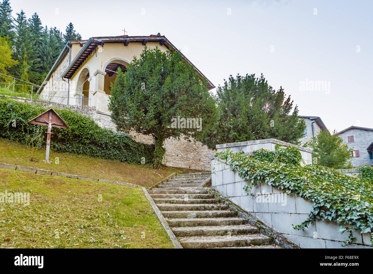 wooden cross near boston ivy in the garden in front of the church in a medieval mountain village in Tuscany Stock Photo