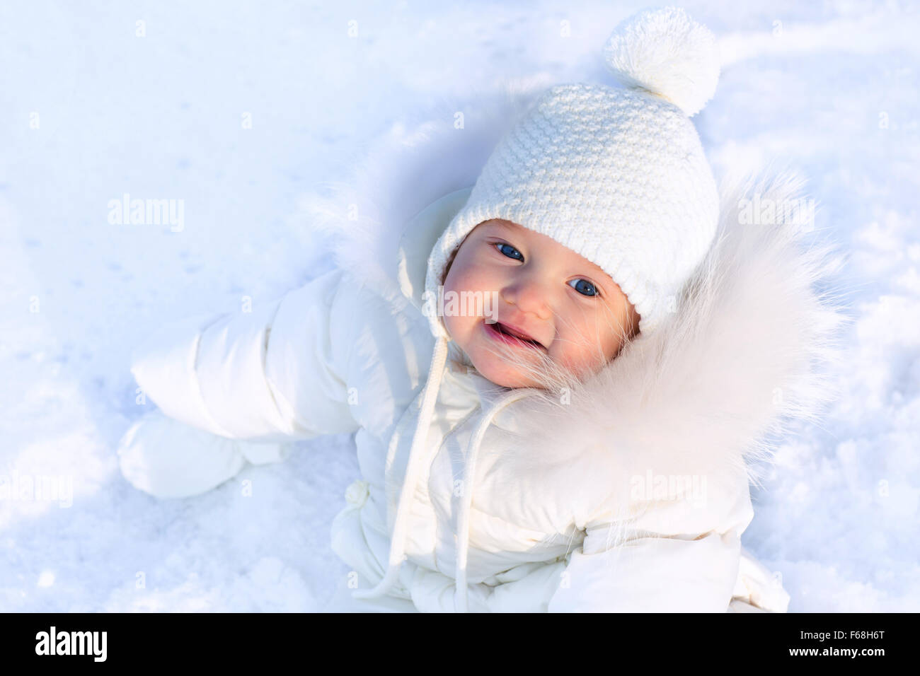 Funny little baby girl in a white knitted hat and warm white coat playing  with snow. Kids play outdoors in winter. Children havi 1294f788d1b
