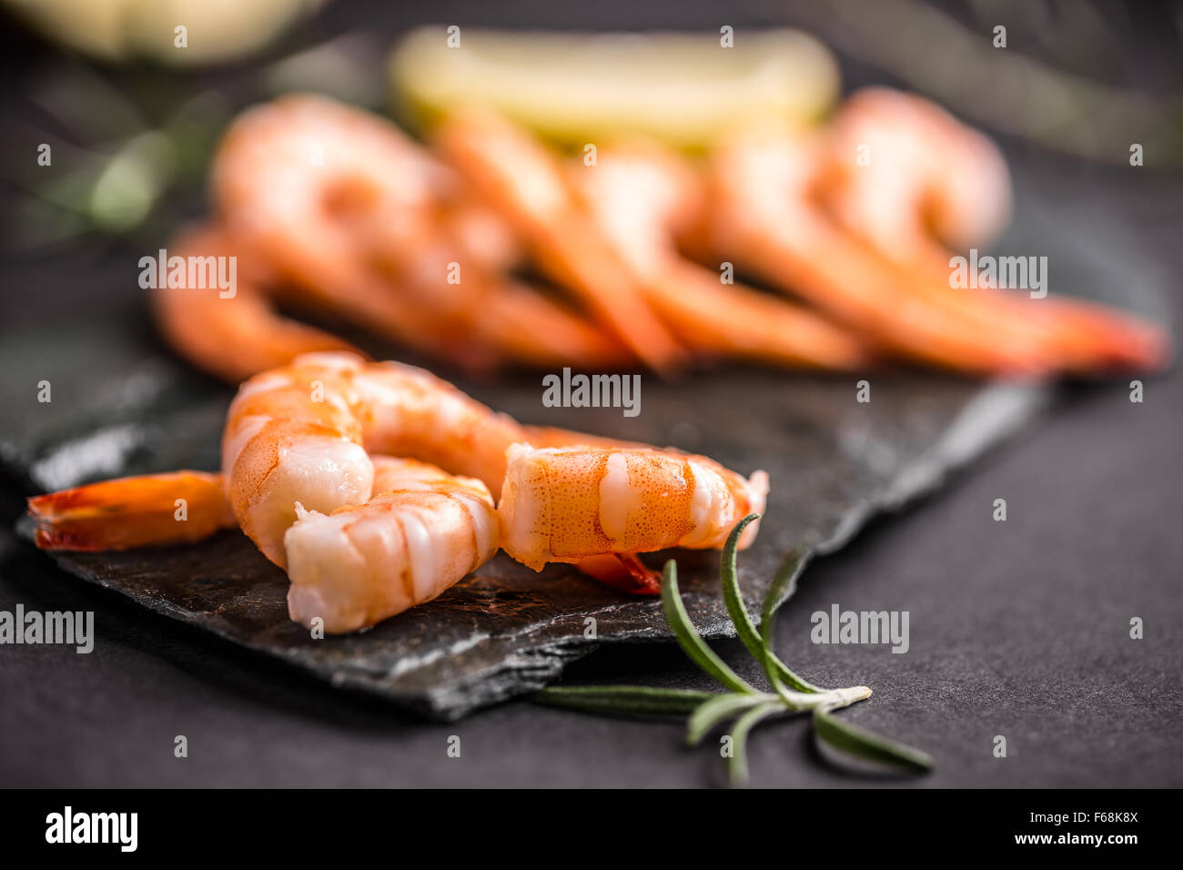 Raw prawns on black slate - Stock Image