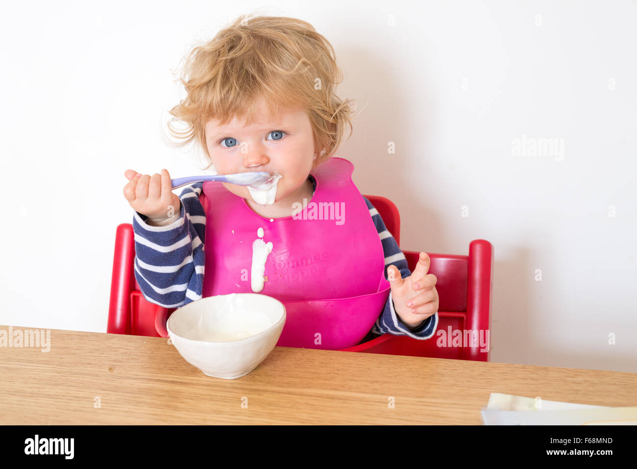 One year old baby eating yoghurt messily with a spoon, England, UK - Stock Image