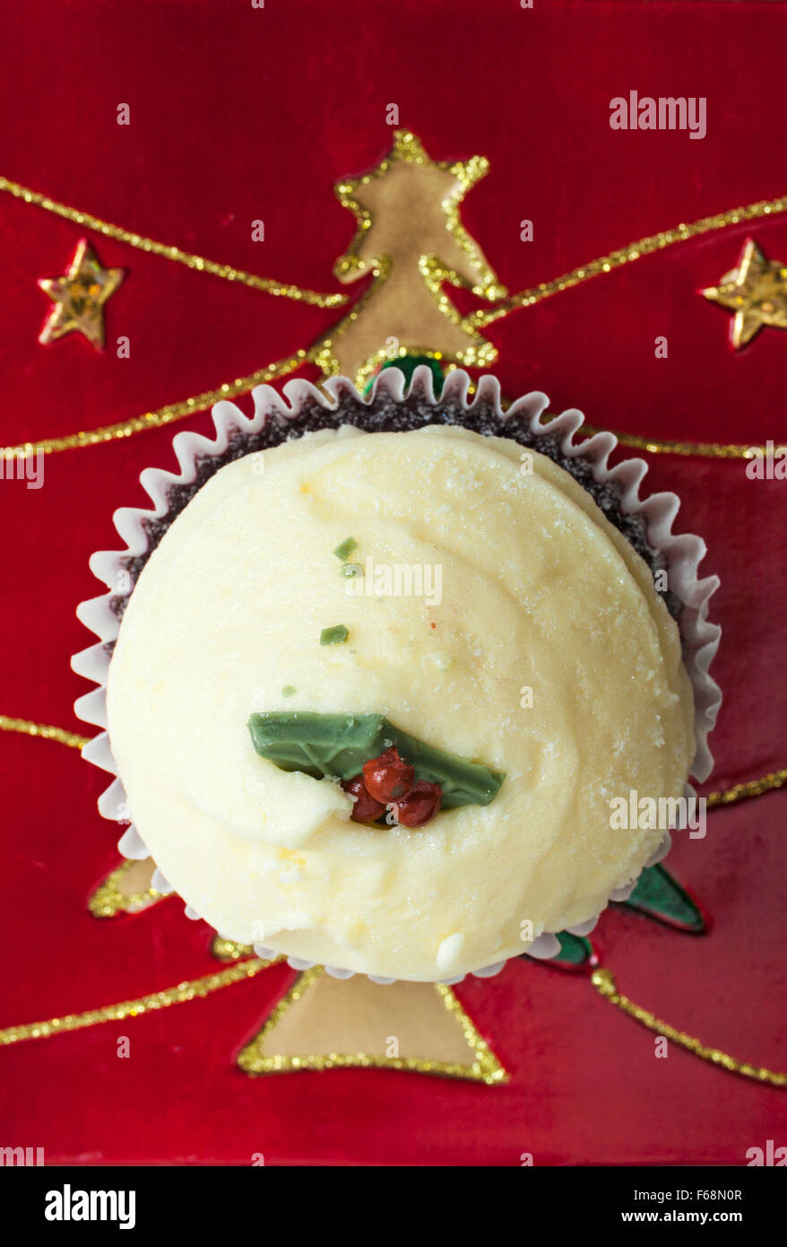 Christmas Pudding Red Velvet muffin on Christmas plate with gold tree and stars Stock Photo