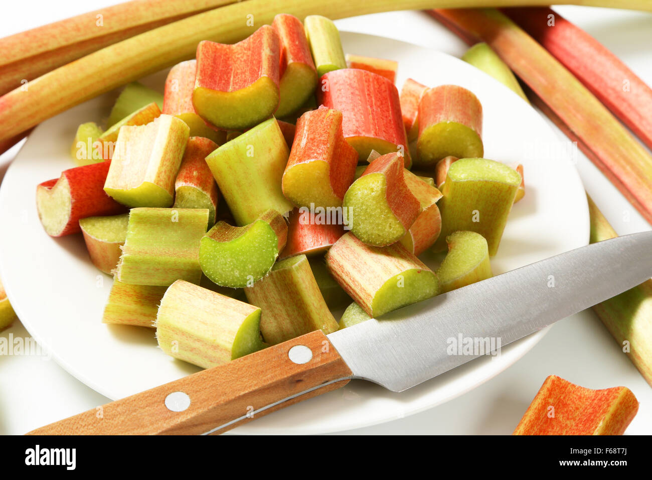 detail of chopped rhubarb on white plate - Stock Image