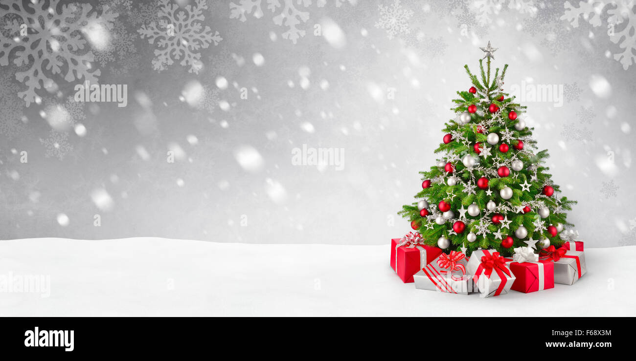 Gorgeous elegant Christmas tree with gifts in red and silver on a panoramic snow background - Stock Image