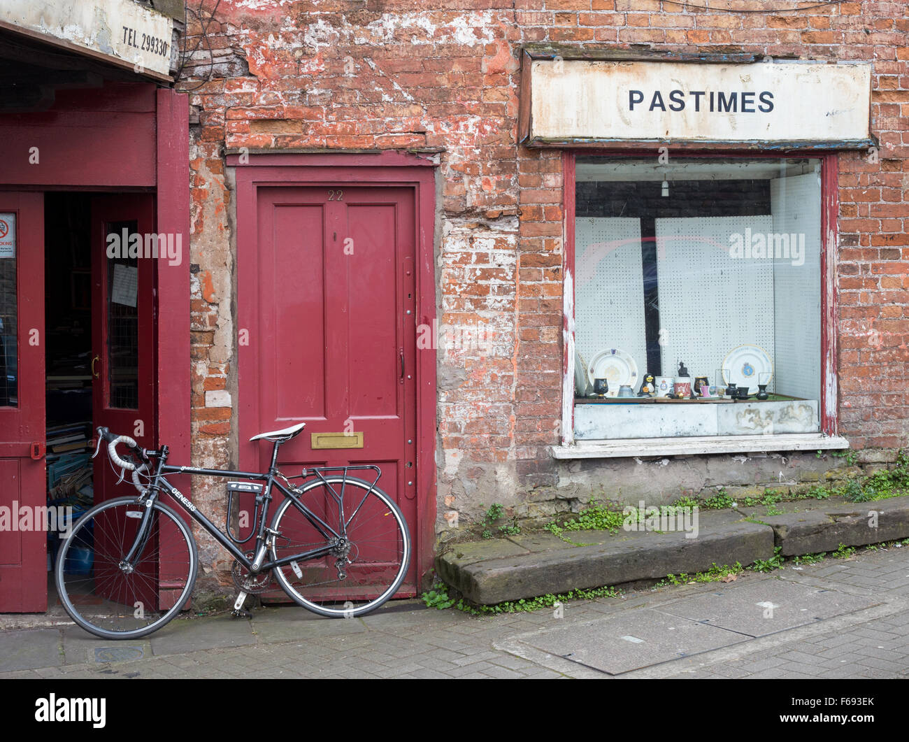 A bicycle outside the window and front door of the Pastimes Bric a Brac Antique shop,Colston Road, Lower Park Row, - Stock Image