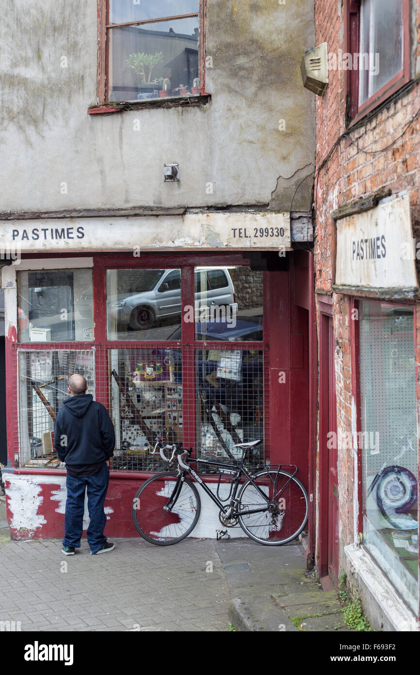 A man looks in the window of the Pastimes Bric a Brac Antique shop,Colston Road, Lower Park Row, Bristol, UK - Stock Image