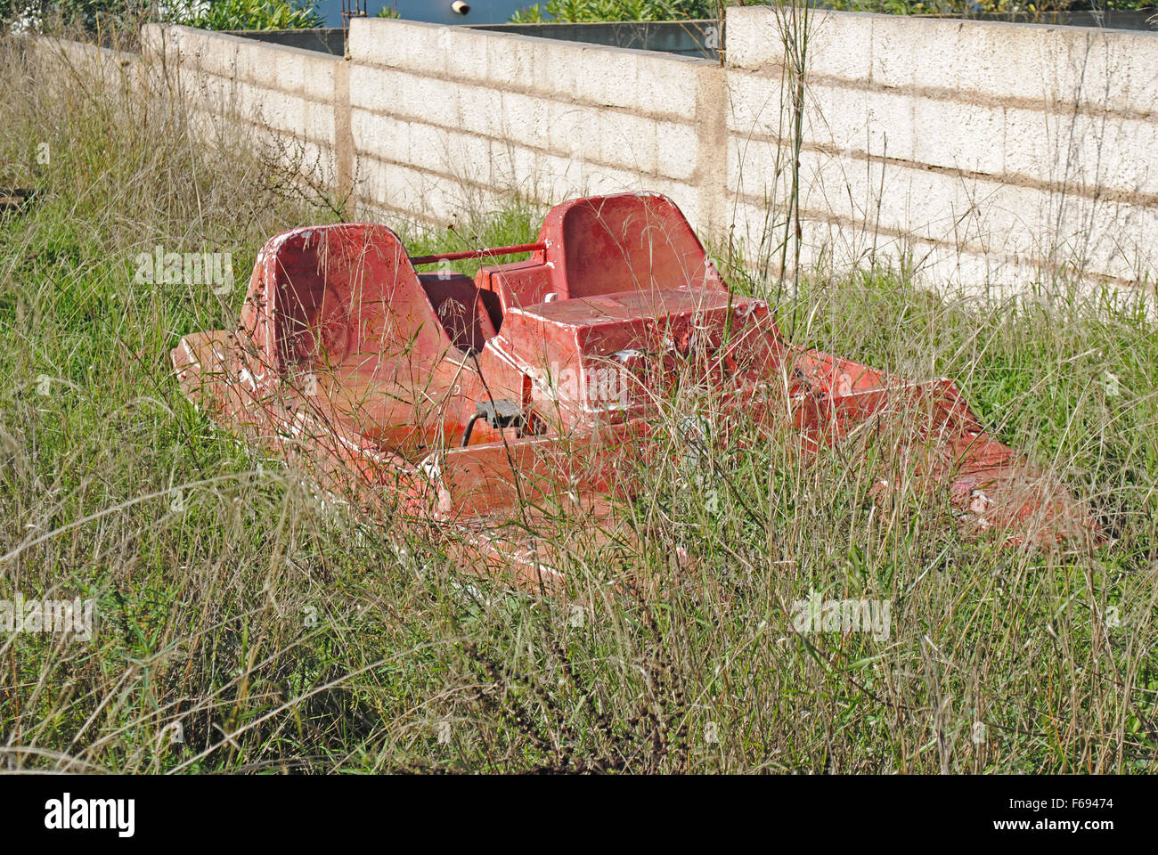 An old red pedalo seen in a neclected garden area. - Stock Image