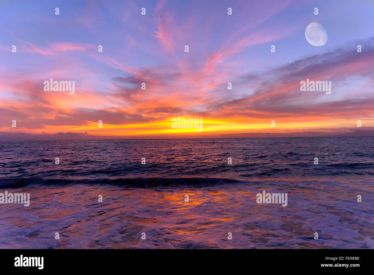 Ocean sunet moon is a colorful cloud filled sky over the ocean with a three quarter moon rising high in the sky. Stock Photo