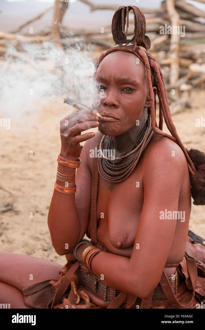 Himba woman smoking pipe, Kaokoveld Namibia - Stock Image