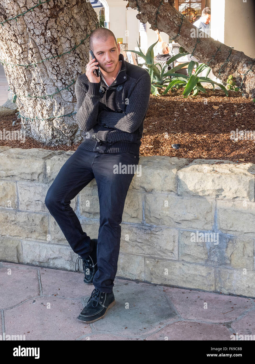 A 20-30 year old male dressed in all black looks straight ahead as he talks on his cell phone in Santa Barbara, - Stock Image