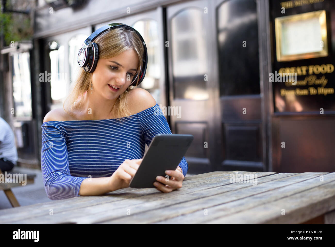 young woman wearing headphones and reading an ebook - Stock Image