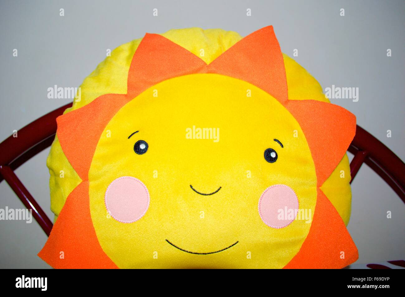 Sunflower shape baby pillow with smily - Stock Image