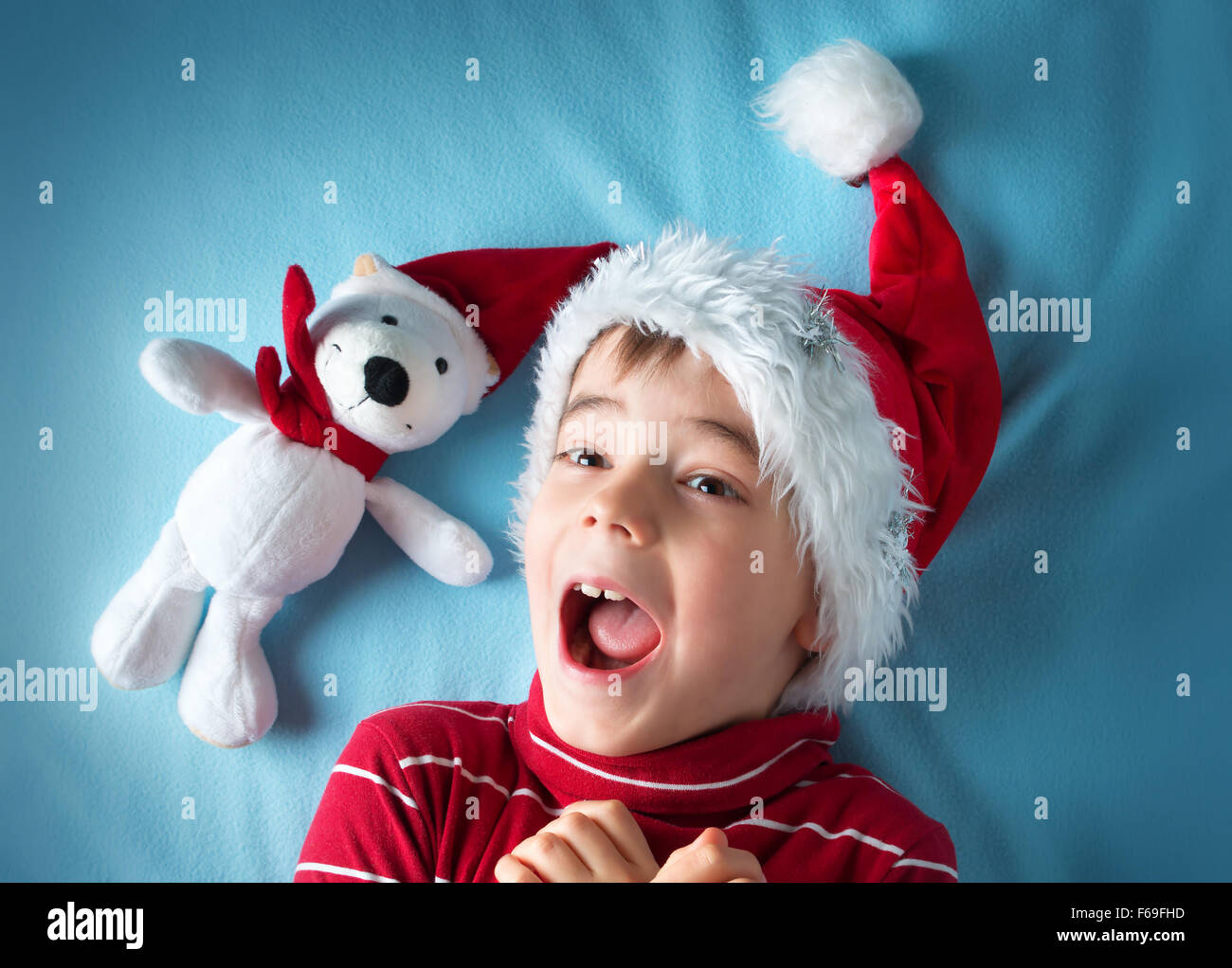 Happy boy in santa claus hat with a white bear on blue background - Stock Image