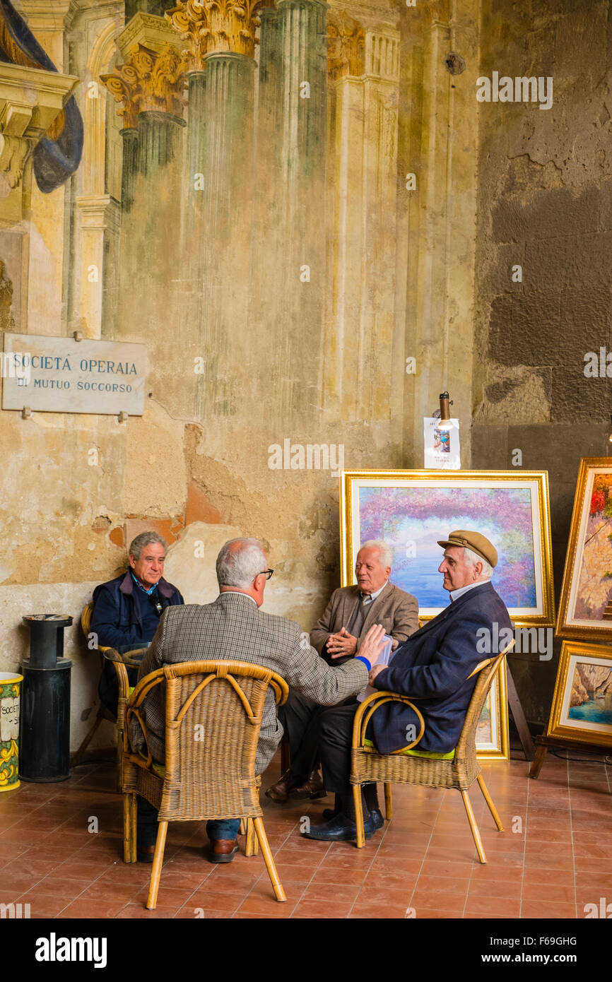 A group of four men sit at a table and converse at the Sorrento Mens' Club. - Stock Image