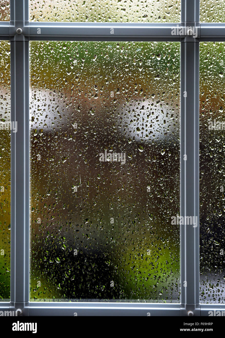 Raindrops on glass window pane on bad weather day UK - Stock Image