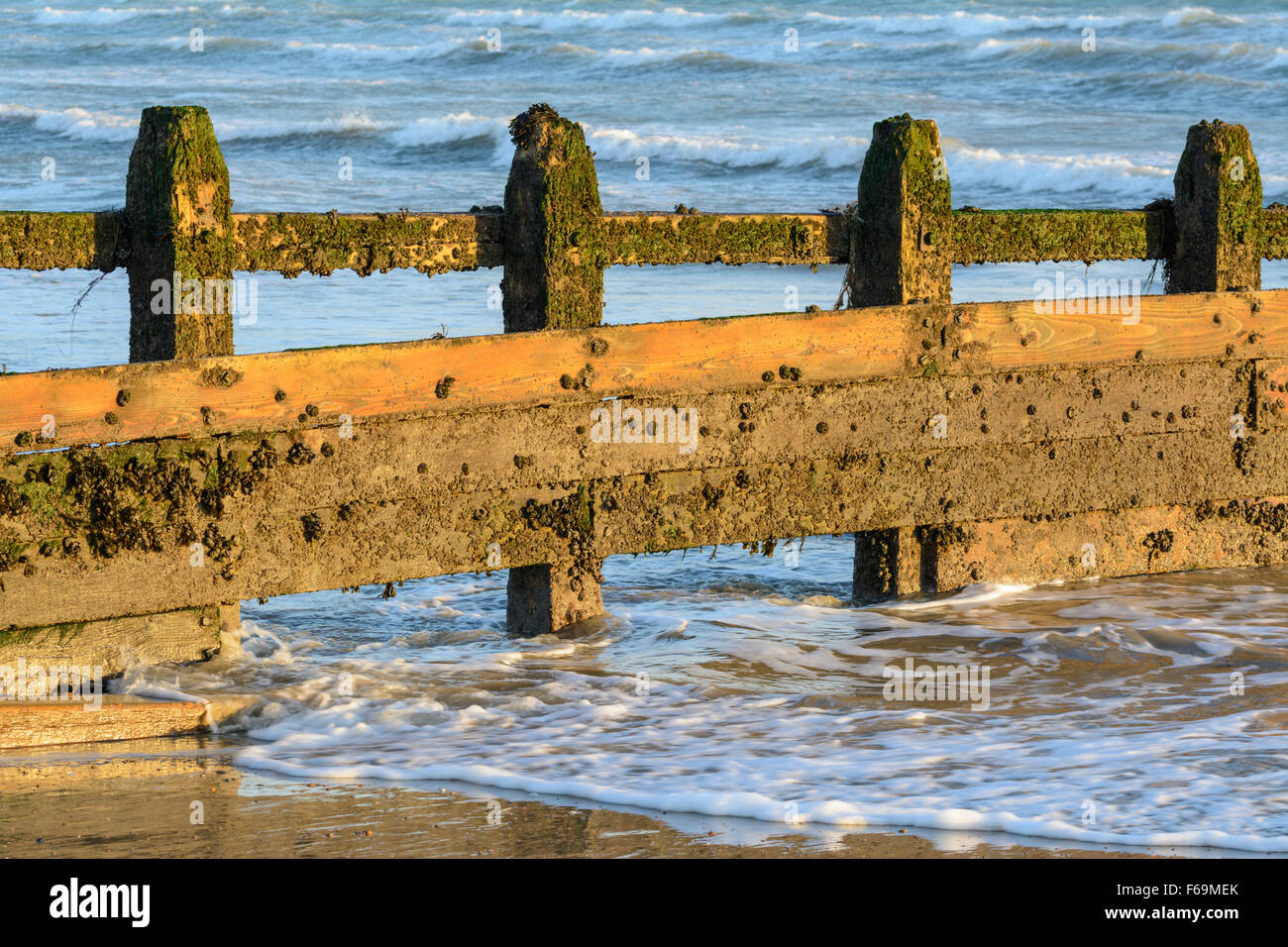 Groyne with a gap and sea passing through it on the beach. - Stock Image