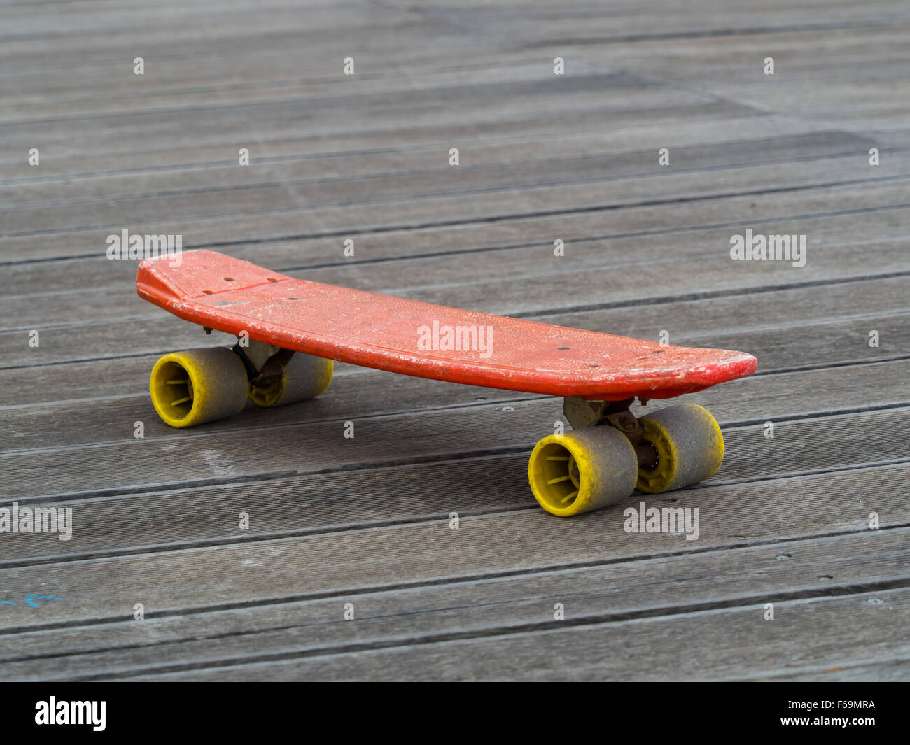 old skate board made of red and yellow plastic on wooden surface - Stock Image