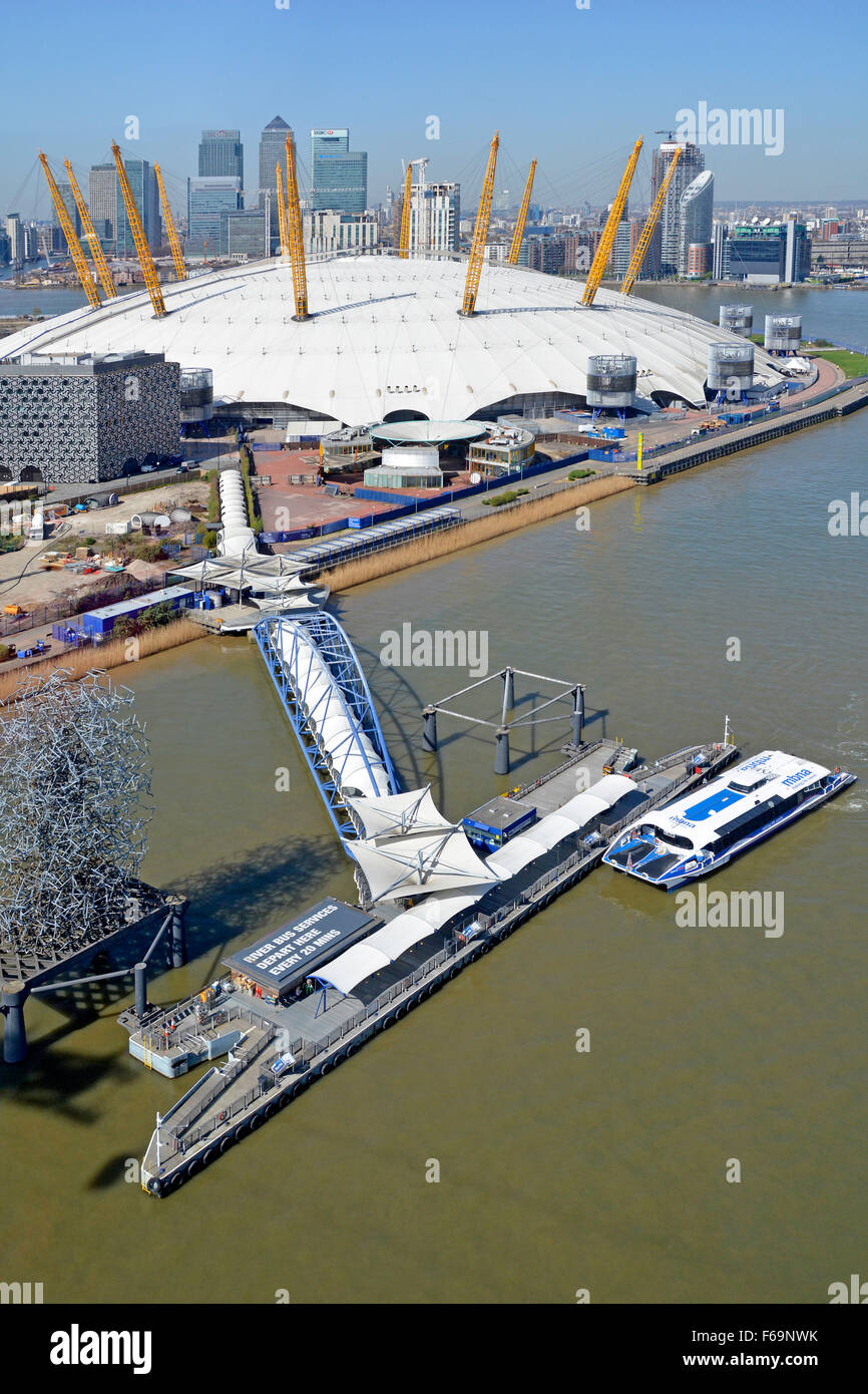 Thames Clipper River Bus service aerial view at North Greenwich Pier with O2 dome & Canary Wharf skyline beyond - Stock Image