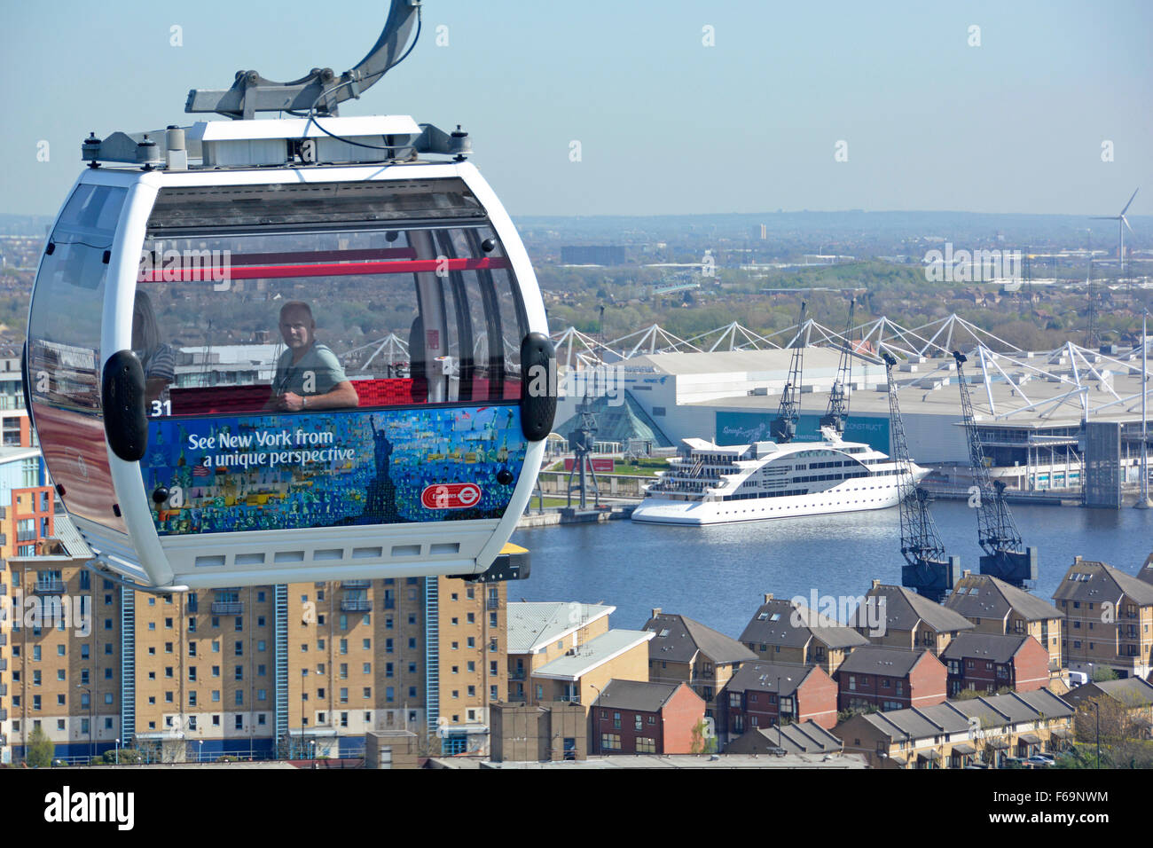 Emirates cable car passengers in cable car crossing over part of London Docklands East London with floating hotel - Stock Image