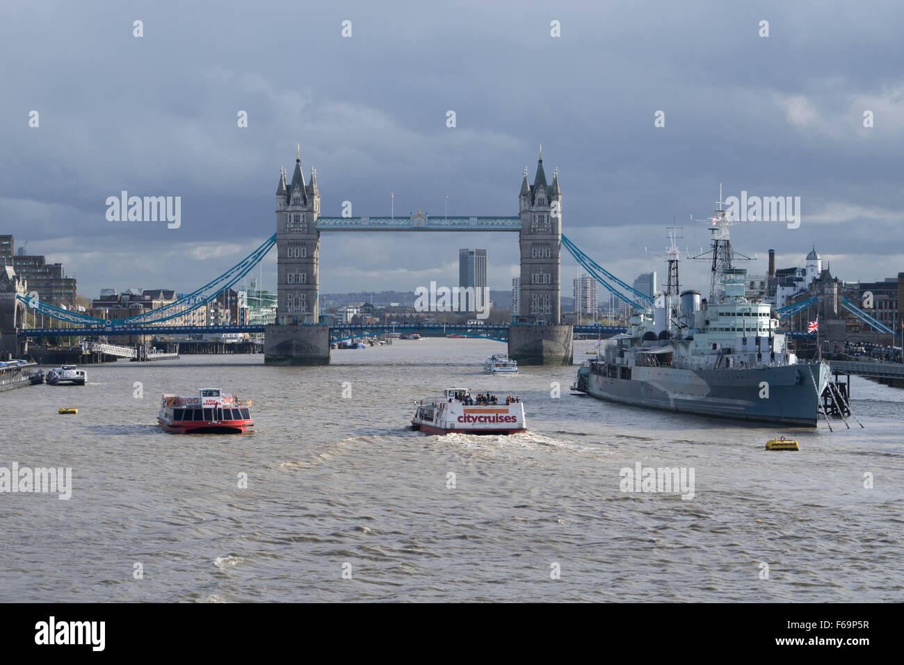 Tower Bridge London with HMS Belfast in the foreground at high tide with tourist pleasure boats - Stock Image