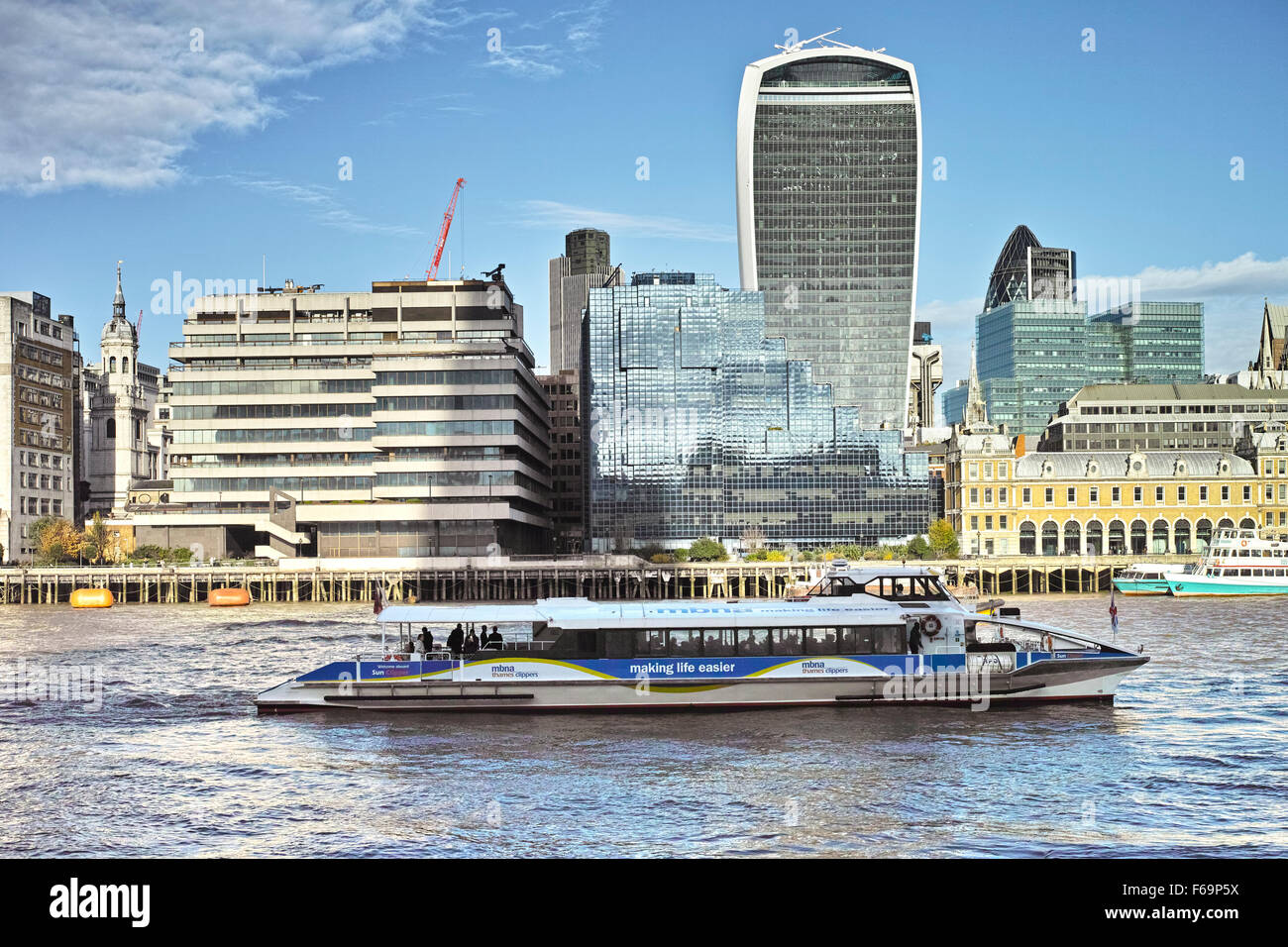 A London Thames Clipper waterbus passes in front of 20 Fenchurch Street and the City of London square mile waterfront - Stock Image