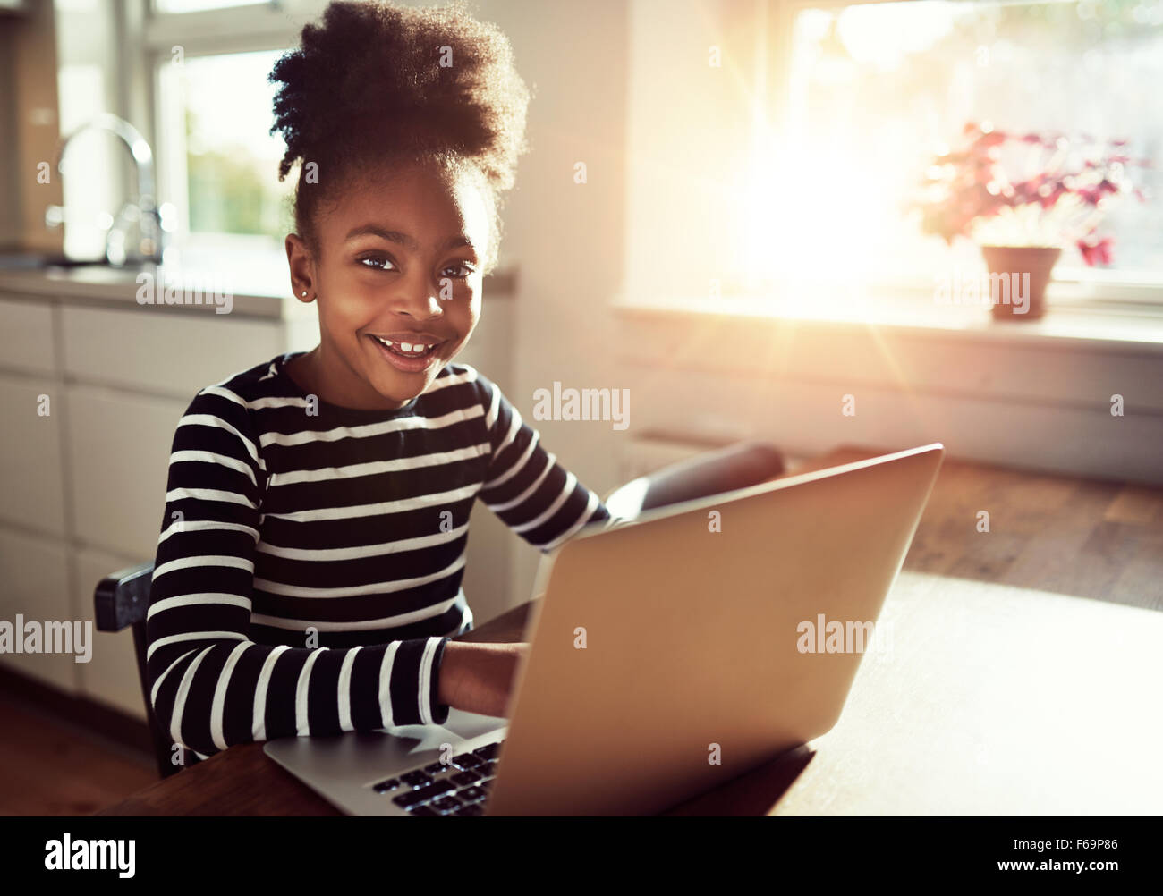 Smiling friendly young black african girl with a cute top knot afro hairstyle sitting at a laptop computer at the - Stock Image