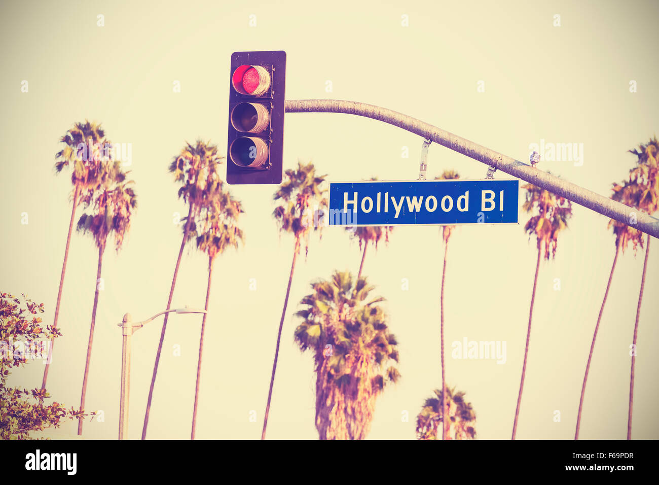 Vintage retro toned Hollywood boulevard sign and traffic lights with palm trees in the background, Los Angeles, - Stock Image
