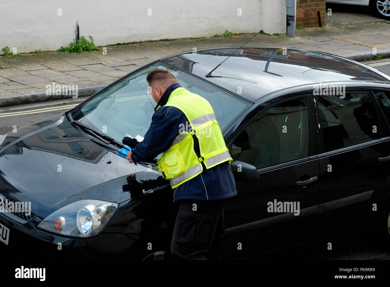 traffic warden issuing a parking ticket for a violation england uk - Stock Image