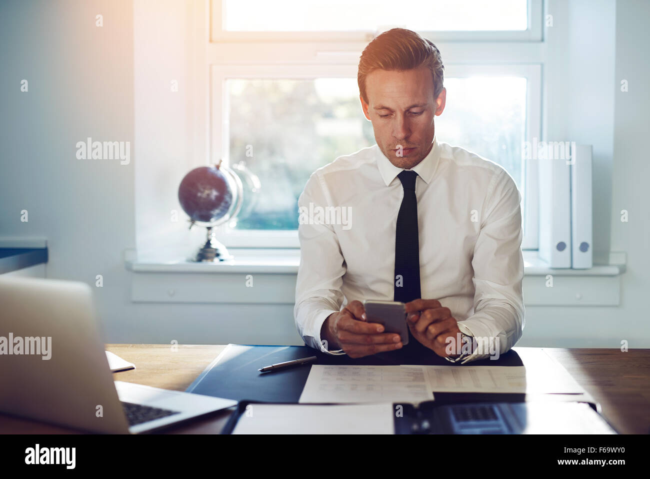 Executive business man texting on his phone and checking mail while sitting at his desk at the office - Stock Image