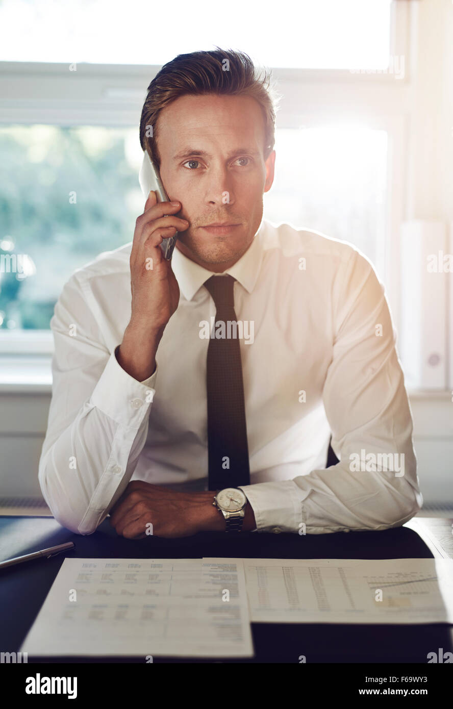 Portrait of business man talking on the phone with documents on the desk - Stock Image