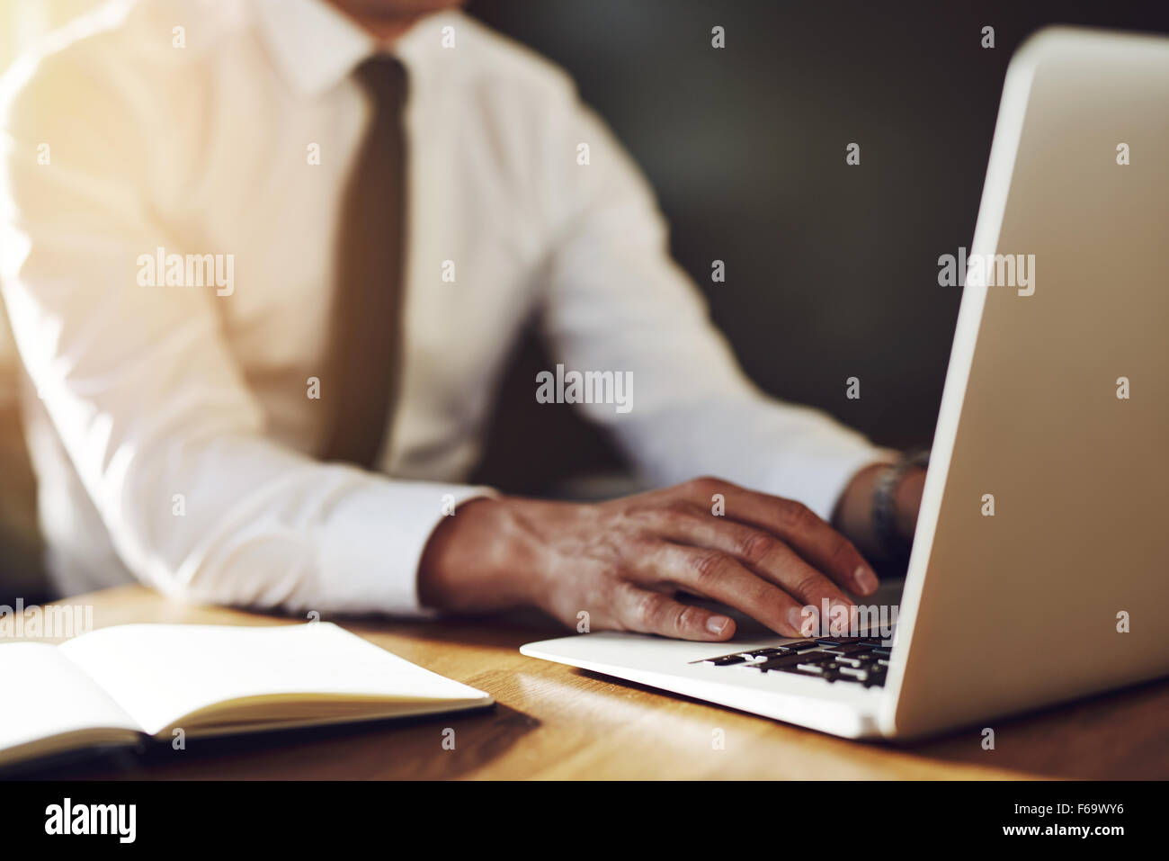 Close up of hands writing at laptop, business concept, white shirt and tie - Stock Image