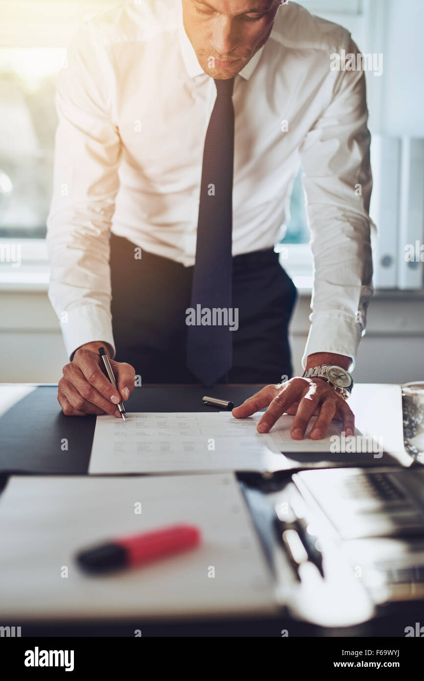 Business man closing a deal signing documents at desk in office wearing white shirt and tie - Stock Image