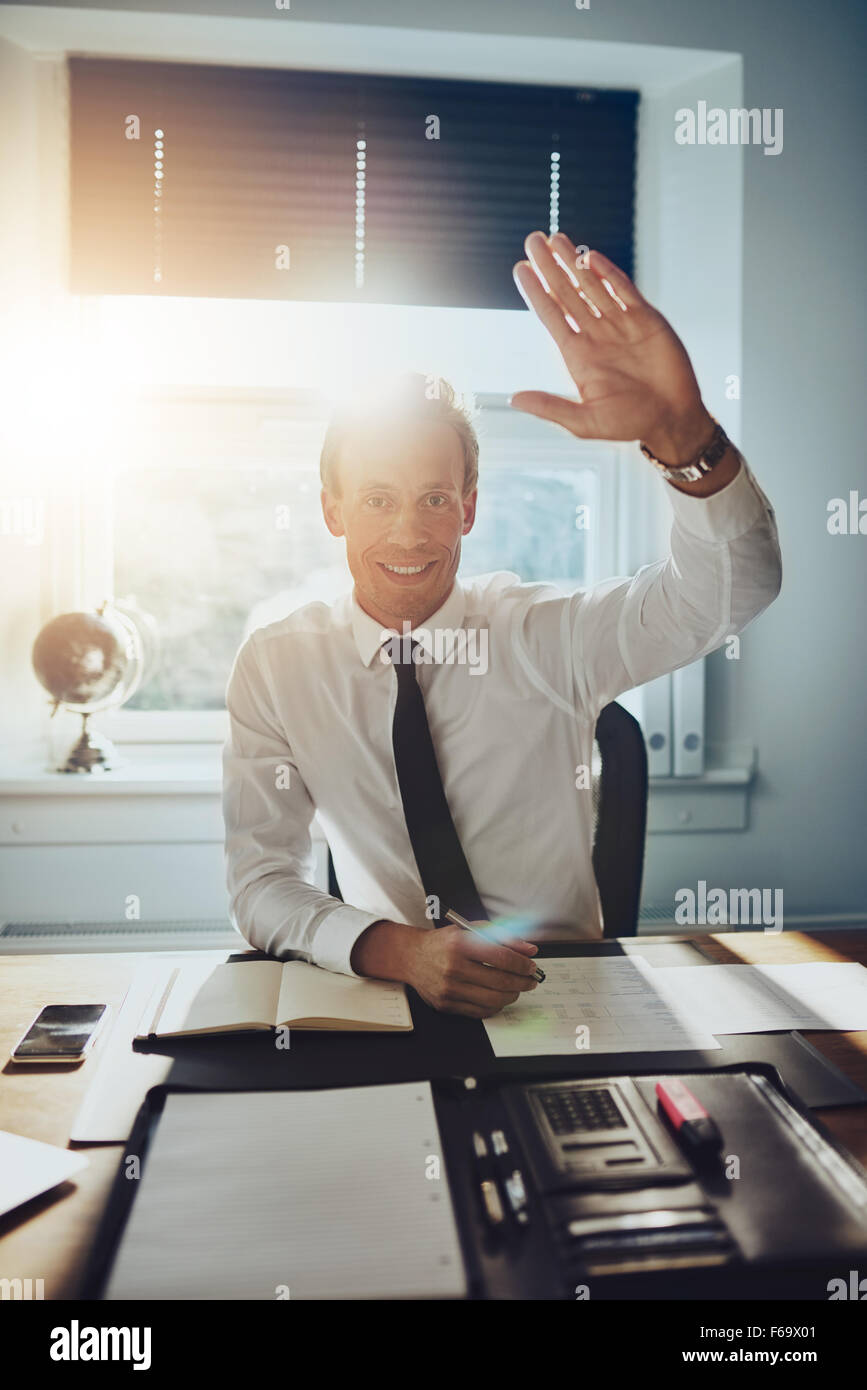 Business man giving high five to camera while smiling, wearing suit and tie - Stock Image