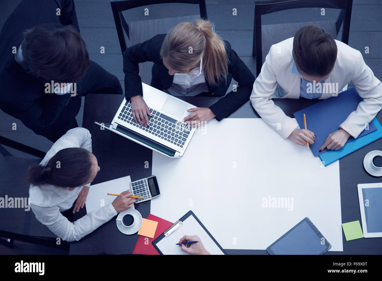 Business workplace with people, cup of coffee, digital tablet, smartphone, papers and various office objects on - Stock Image