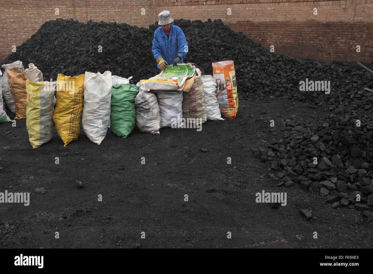 A woman bags blocks of coal at a coal store in a village in GuAn, 50km to Beijing, Hebei province, China. - Stock Image