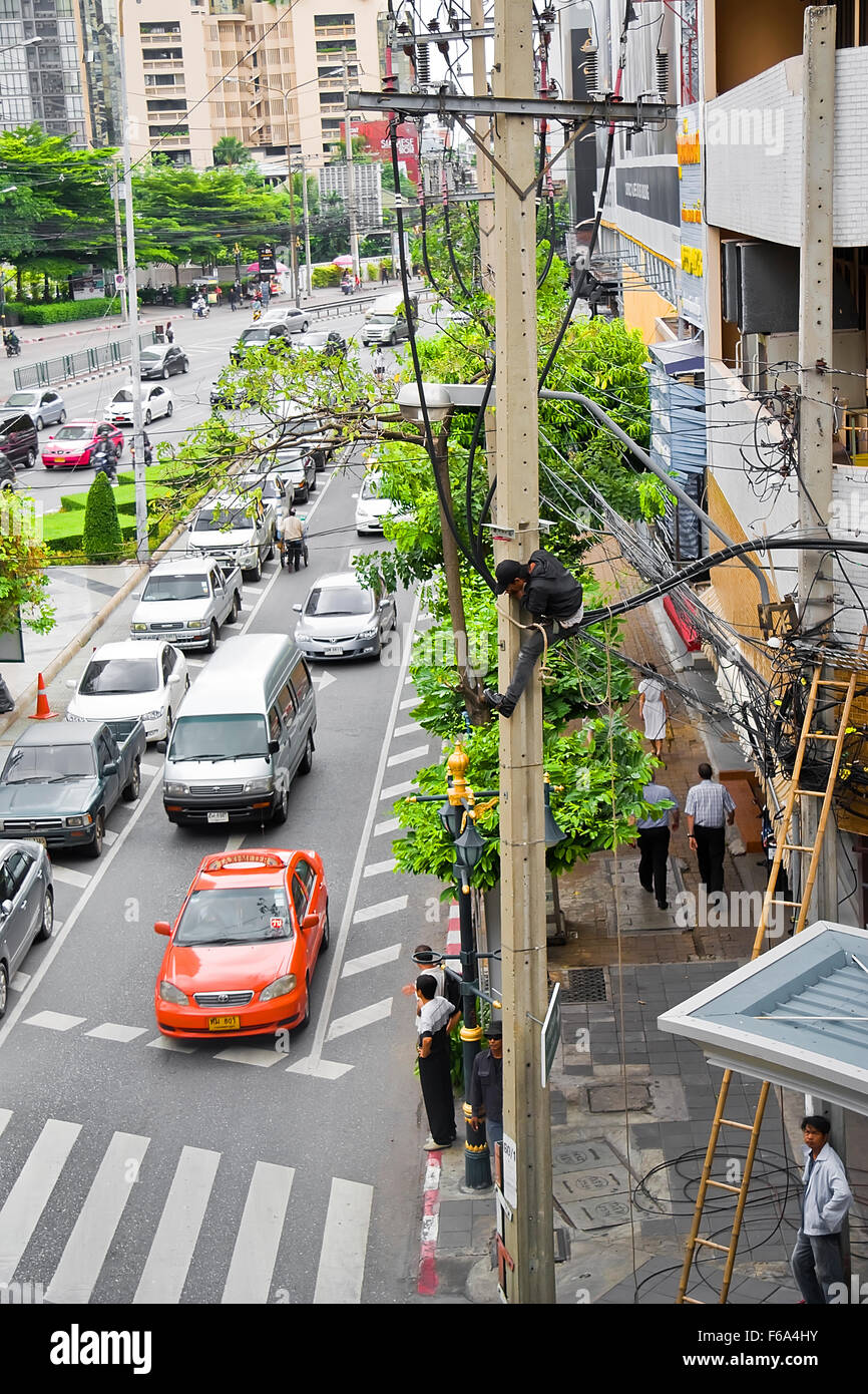 Image of a Thai electrician (linesman) working on overhead cables in Bangkok - Stock Image