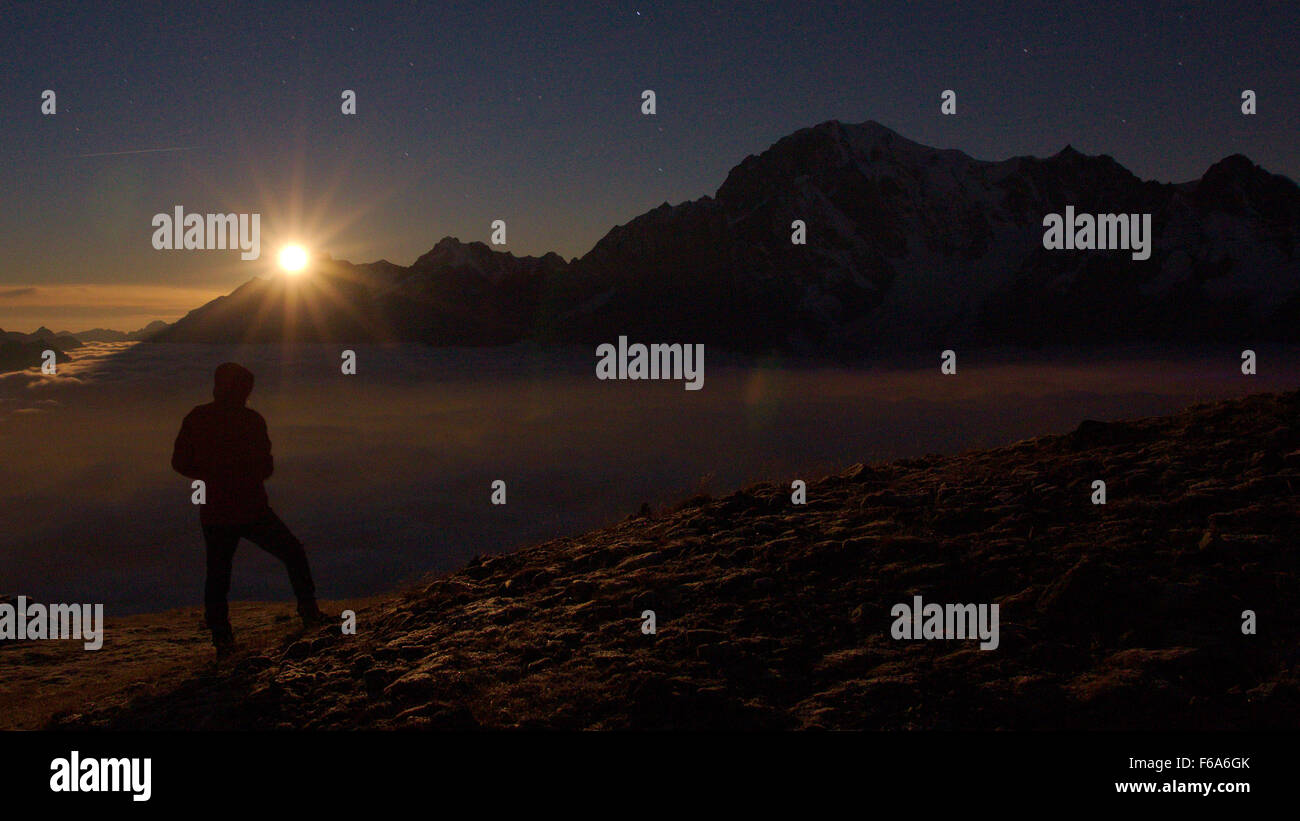 Climber silhouette in front of Monte Bianco during moon sunset - Stock Image
