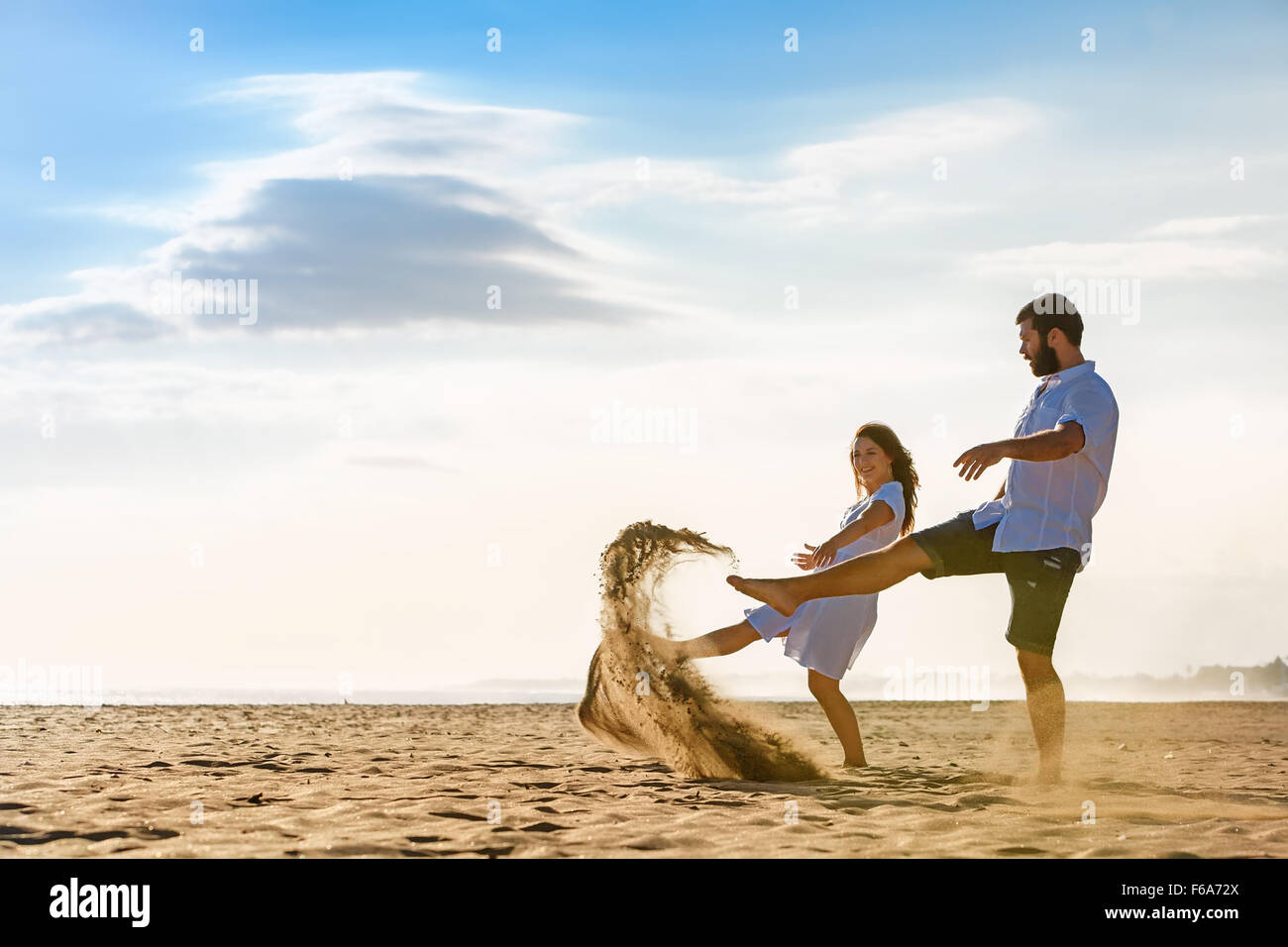 Happy newlywed family on honeymoon holidays - just married loving wife and husband run with fun on sea sand beach. - Stock Image