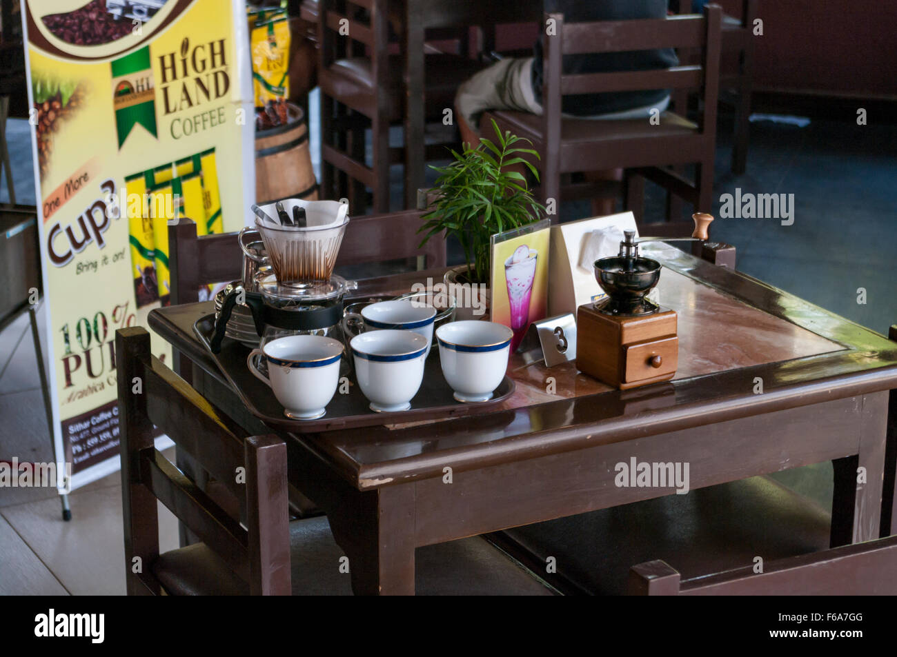 Set to prepare freshly brewed coffee in a cafe in Pyin Oo Lwin, Myanmar, consisting of cups, a coffee grinder and - Stock Image