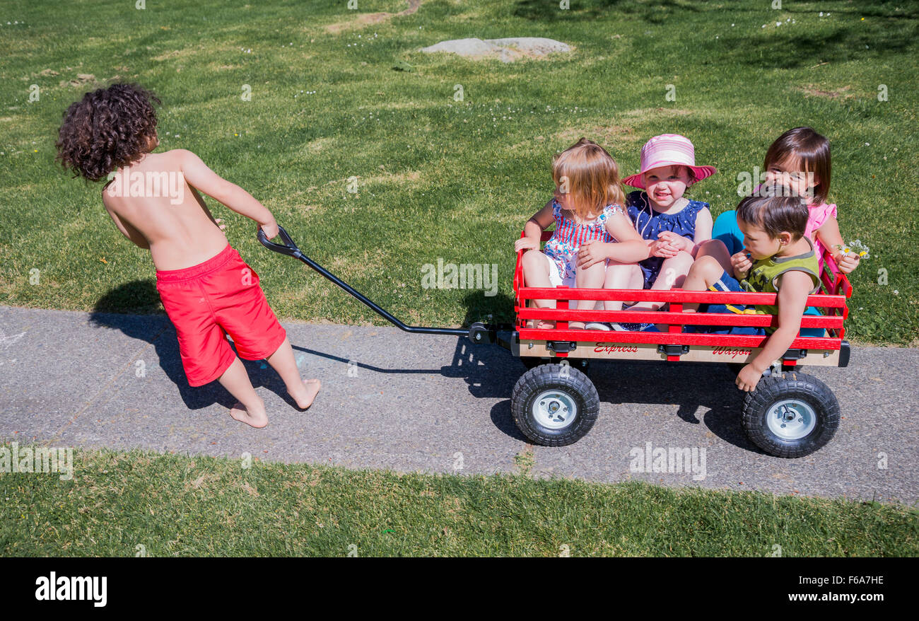 Boy pulling other kids on wagon. - Stock Image