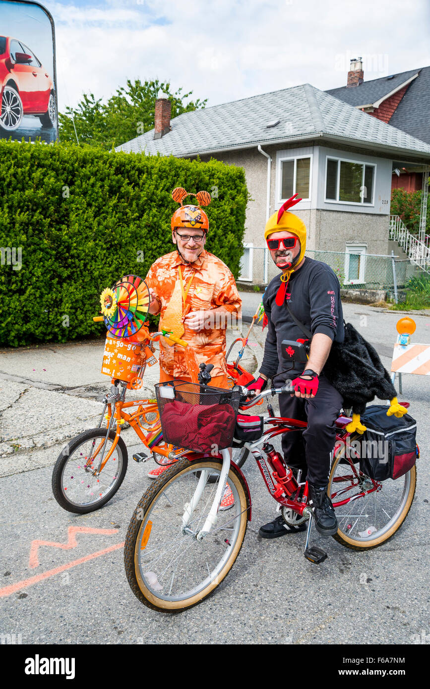 Two men in silly costumes on bicycles. Car free day, Main Street area, Vancouver, British Columbia, Canada, - Stock Image