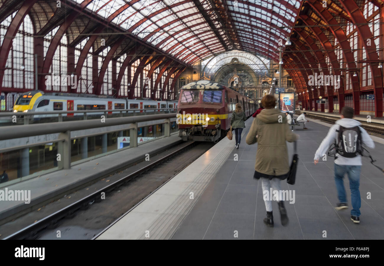 Several young people rushing towards a train whose departure is imminent. Overground platform in Antwerp train station. - Stock Image