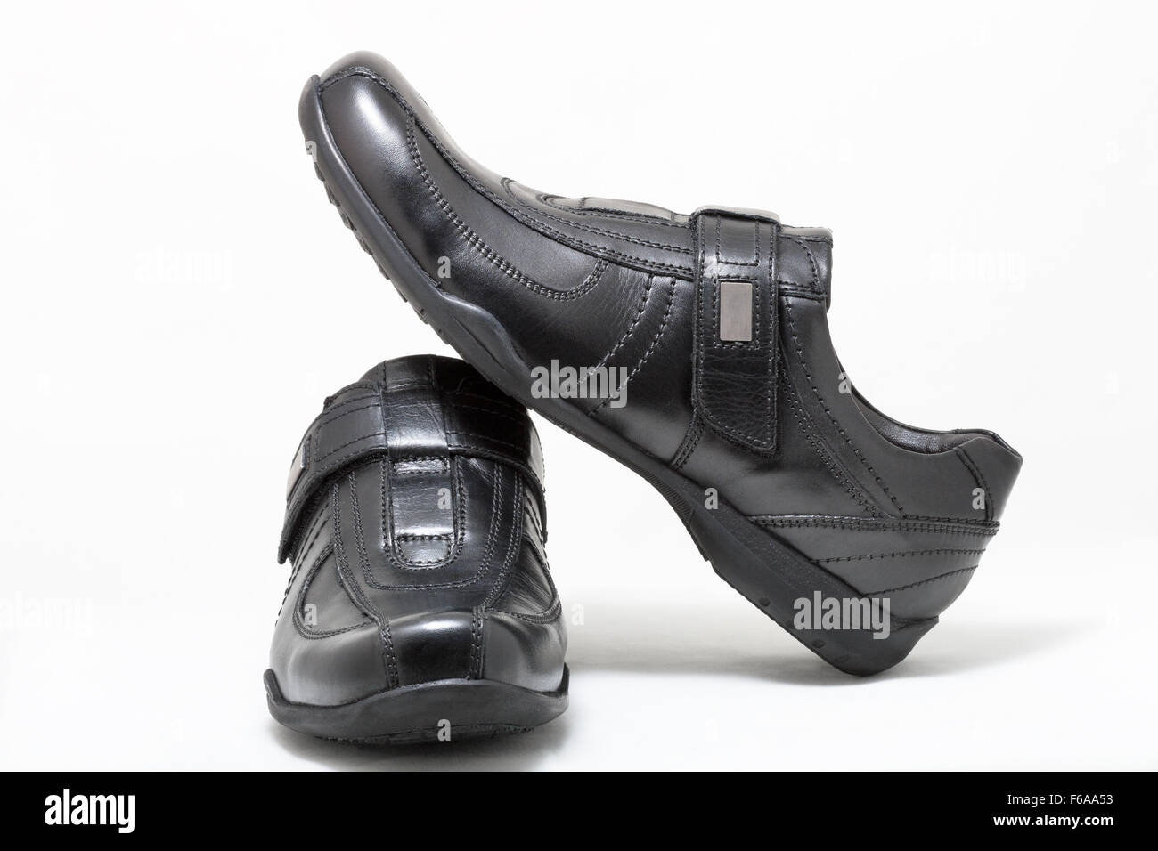 Pair of black man leather shoes with velcro on white background - Stock Image