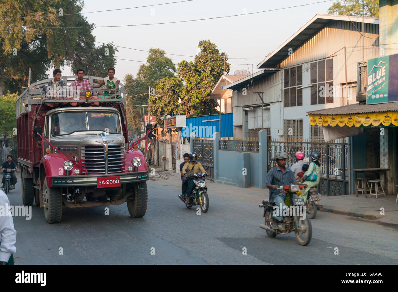 Busy street in Amarapura, Myanmar. Main subject is a truck with people sitting on top. - Stock Image