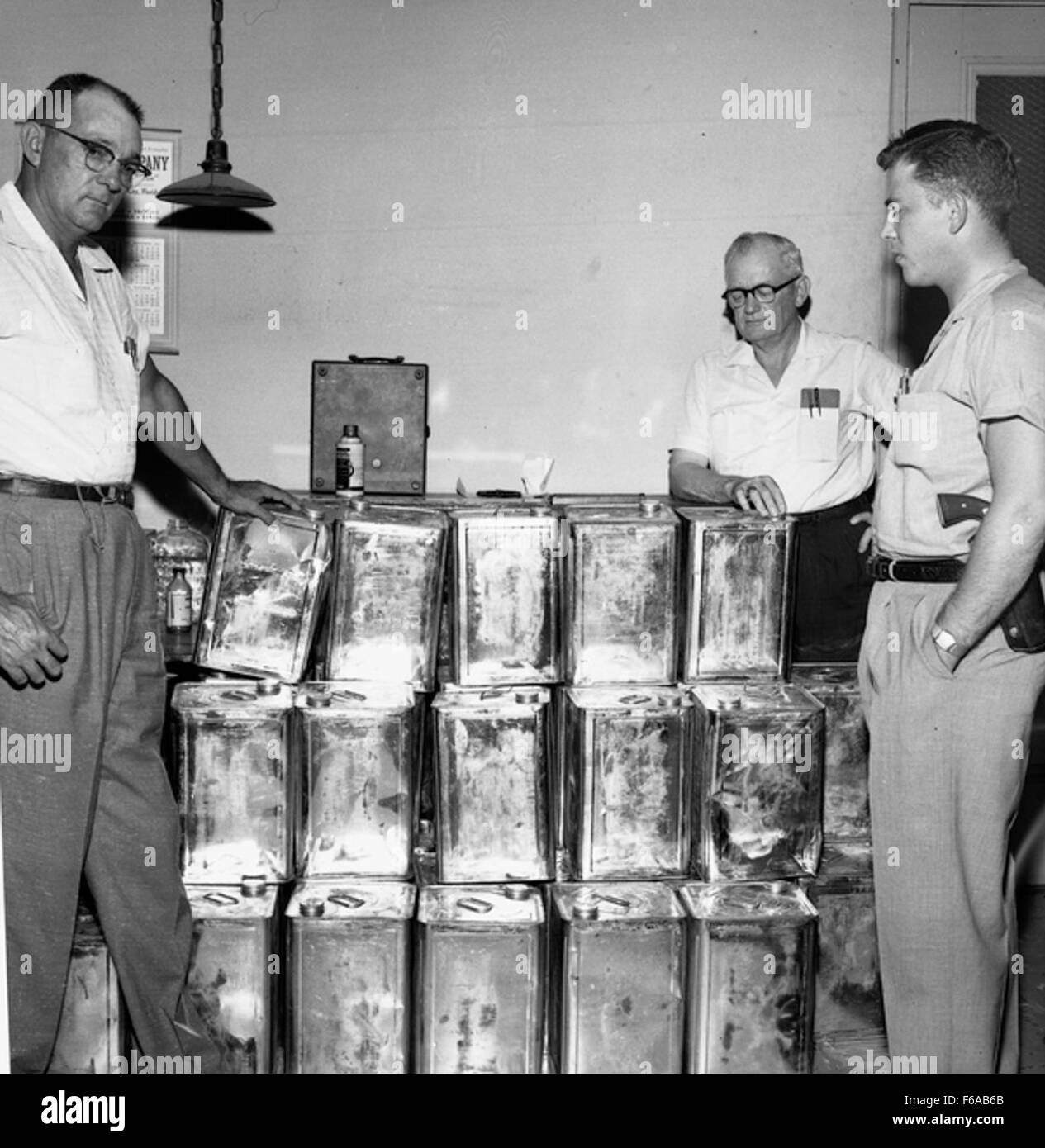 Law enforcement officers with moonshine seized during a raid, Tallahassee - Stock Image