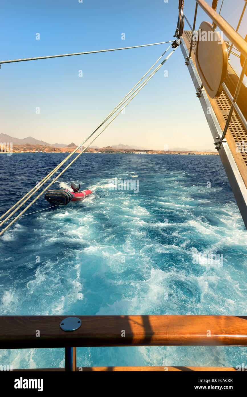 Wooden sailboat tows rubber boat in the sea - Stock Image